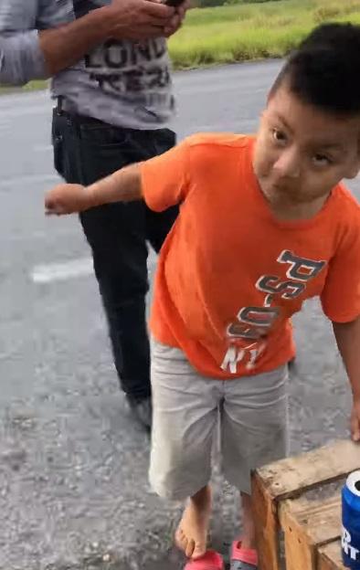 niño compra naranjas